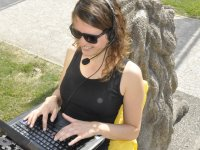 Student outside with laptop and headset