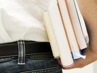 Rückensicht eines Mannes mit Bücherstapel unterm Arm