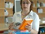 Bibliotheksmitarbeiterin verbucht Bücher im Ausleihsystem