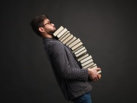 Man balancing a stack of books