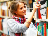 Young woman pulling books from shelf