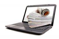 Laptop mit Zeitschriftenstapel auf dem Desktop