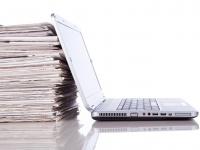 Laptop mit Zeitschriftenstapel