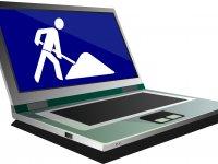 Grafik eines Laptops, auf dessen Bildschirm das blau-weiße Piktogramm einer Baustelle zu sehen ist.