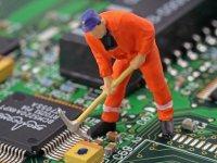Miniatur-Bauarbeiter steht mit der Spitzhacke auf einer freiliegenden Computerfestplatte