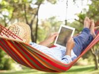Mann mit Strohhut und Tablet in einer Hängematte liegend