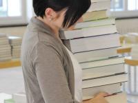 Frau mit Bücherstapel