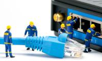 Miniaturfiguren mit Internet-Kabel vor einem Switch-Gerät
