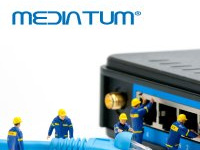 Miniature figures with internet cable in front of a switch box and mediaTUM writing above