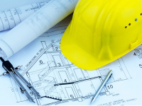 Construction plans and yellow safety helmet