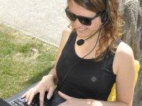 Studentin mit Laptop, Headset und Sonnenbrille draußen im Grünen