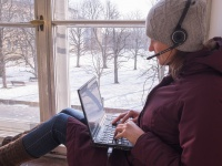 Woman sits with laptop on windowsill