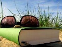 Buch und Sonnenbrille im Sand, im Hintergrund Gras