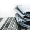 Tageszeitungen und Laptop