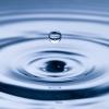 Wassertropfen fallen auf Wasseroberfläche und bilden Wellen