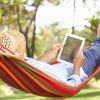 Man with straw hat and tablet relaxing in a hammock
