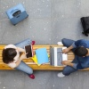 Two students with notebooks and tablets on a bench photographed from above