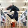 Frau springt zwischen Bücherregalen hoch