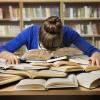 Frau liegt mit Kopf auf Bücherstapel